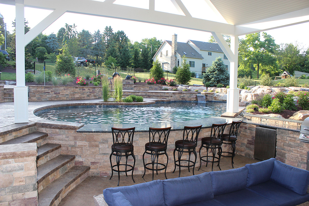 Stamped concrete pool with swim-up bar, fireplace and waterfall