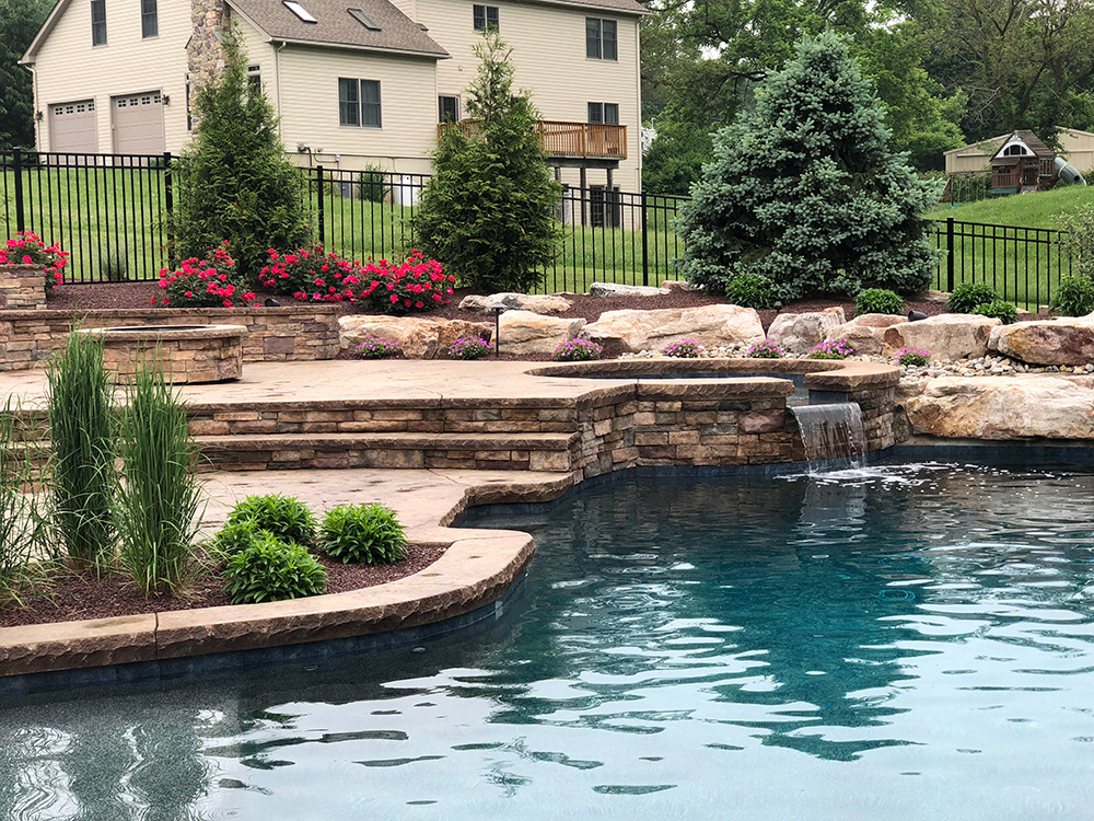 Decorative concrete pool design with waterfull and landscaping