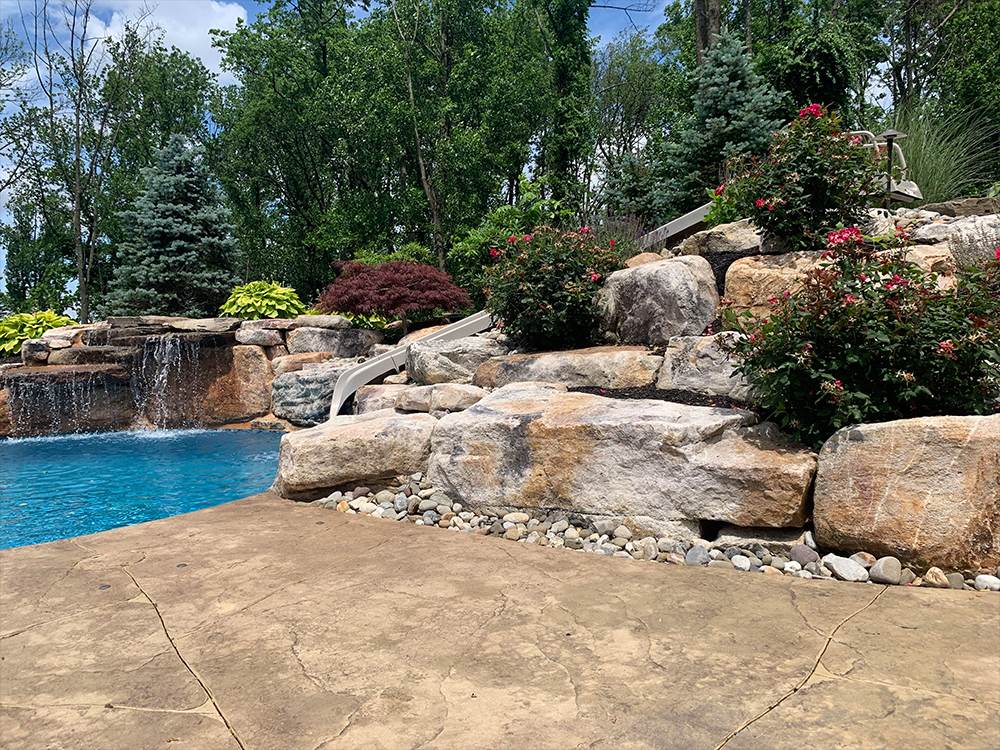 Stamped concrete pool with boulder waterfall